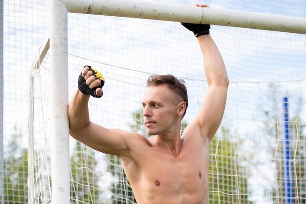 Мускулистый мужчина на футбольном поле, возле стойки ворот. для любых целей.