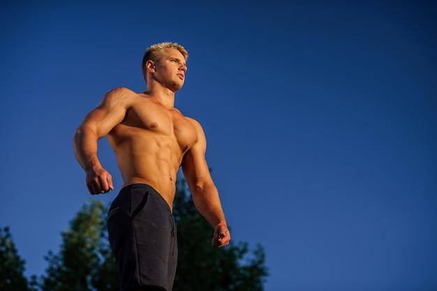 Мускулистый мужчина на крыше во время заката уверен в здоровом образе жизни