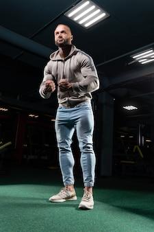 Мускулистый мужчина позирует в тренажерном зале в джинсах и толстовке