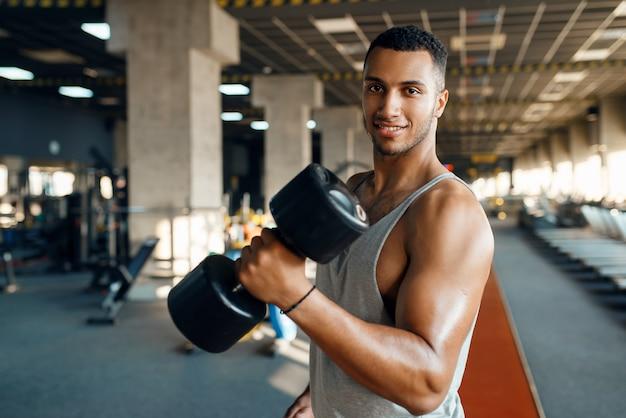 Мускулистый мужчина позирует с тяжелыми гантелями на тренировке в тренажерном зале