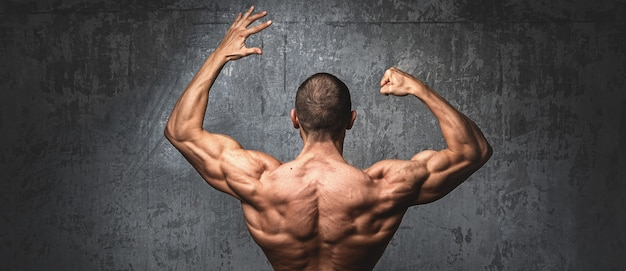 Muscular man  posing against stone wall