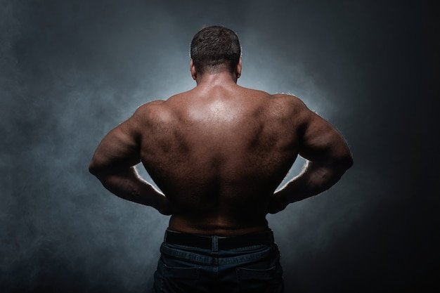 Muscular man posing on black background showing his back in smoke