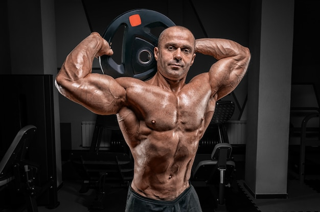 Muscular man posing in the gym with a barbell disc. bodybuilding and powerlifting concept.