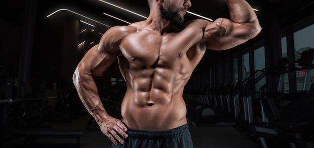 Мускулистый мужчина позирует в тренажерном зале. концепция фитнеса.