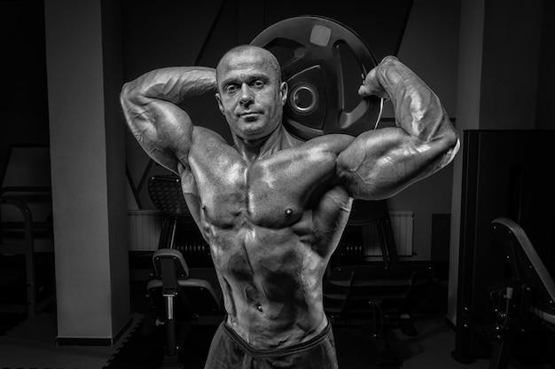 바벨 디스크와 함께 체육관에서 포즈를 취하는 근육 질의 남자. 보디 빌딩 및 파워 리프팅 개념입니다. 혼합 매체