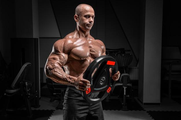 Мускулистый мужчина позирует в тренажерном зале с диском со штангой. концепция бодибилдинга и пауэрлифтинга. Premium Фотографии