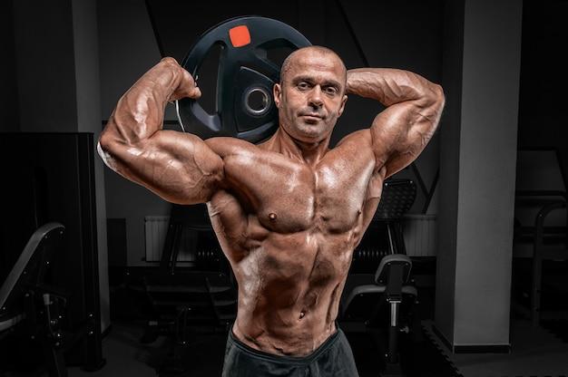 Мускулистый мужчина позирует в тренажерном зале с диском со штангой. концепция бодибилдинга и пауэрлифтинга.