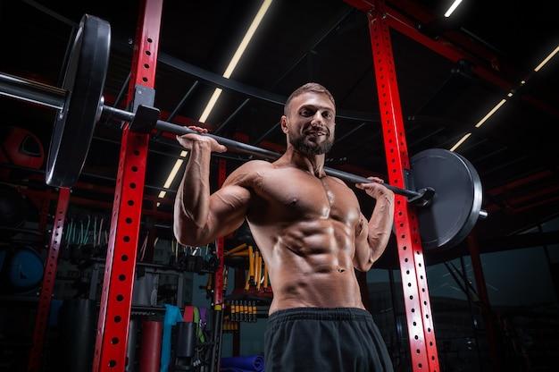 Мускулистый мужчина позирует в тренажерном зале со штангой. концепция фитнеса.