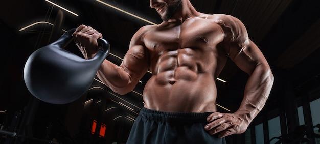 Мускулистый мужчина позирует в тренажерном зале с гирей. концепция фитнеса. смешанная техника