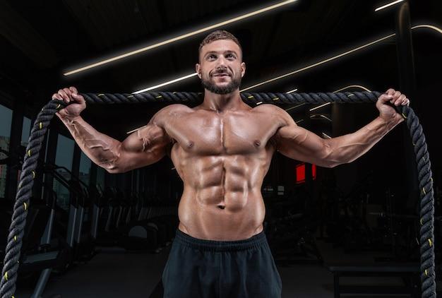 밧줄으로 체육관에서 포즈 근육 남자. 피트니스 개념.