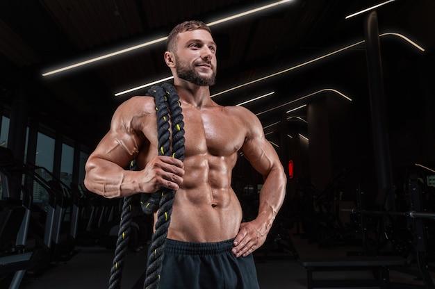 Мускулистый мужчина позирует в тренажерном зале с веревкой. концепция фитнеса.