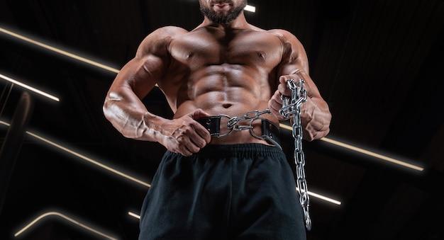 Мускулистый мужчина позирует в тренажерном зале с спортивным поясом. концепция фитнеса.