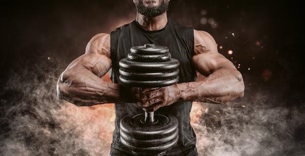 Мускулистый мужчина позирует с гантелями на фоне огня и дыма. концепция фитнеса и бодибилдинга. смешанная техника