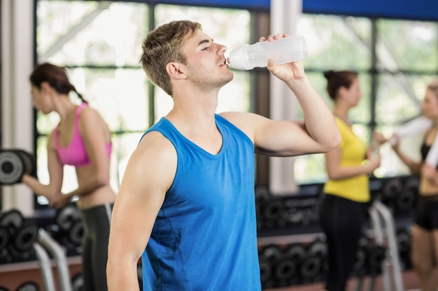 Muscular man posing with athletic women behind at gym