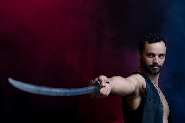 黒とスモークの背景に分離された長い剣でポーズをとる筋肉男