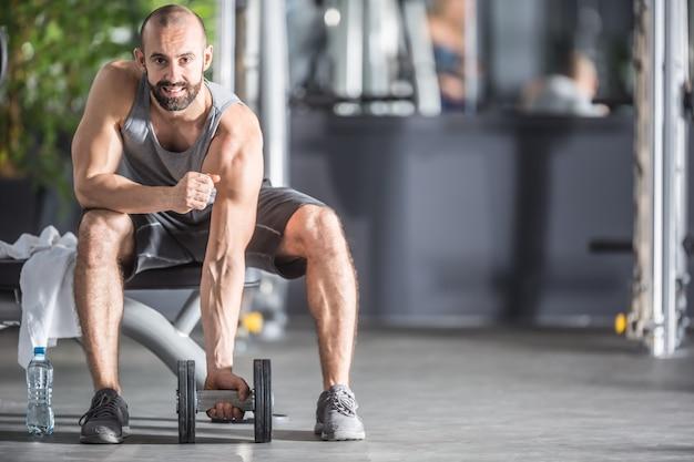 피트니스 체육관에서 아령으로 연습하는 근육질의 남자.