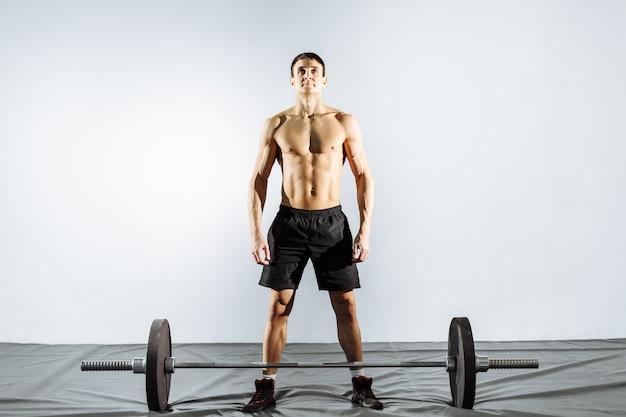 Muscular man preparing to do deadlift.