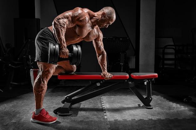 Мускулистый мужчина тянет гантель к животу. концепция бодибилдинга и пауэрлифтинга. Premium Фотографии