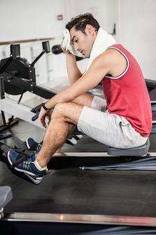 Muscular man on rowing machine wiping sweat with towel in the gym