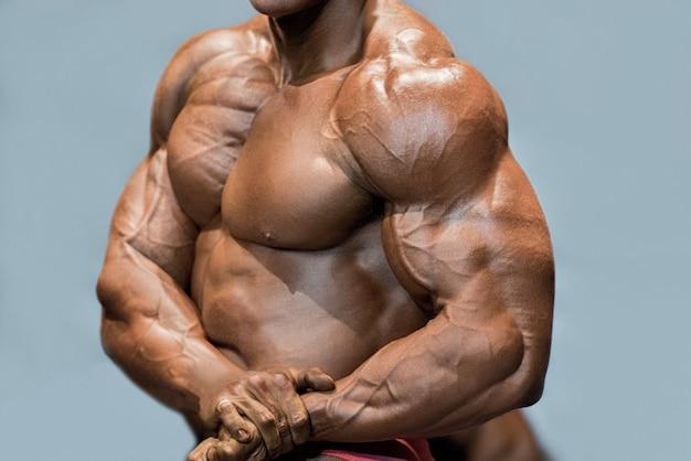 근육질 남자의 옆 가슴 포즈. 파란색 배경에 포즈 보디입니다. 찢어진 근육의 확대 그림입니다. 다이어트가 핵심입니다.