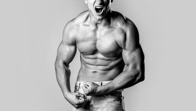 근육 질의 남자 비명. 잘 훈련 된 몸, 팔뚝, 복근 및 근육을 가진 비명을 지르는 남자.