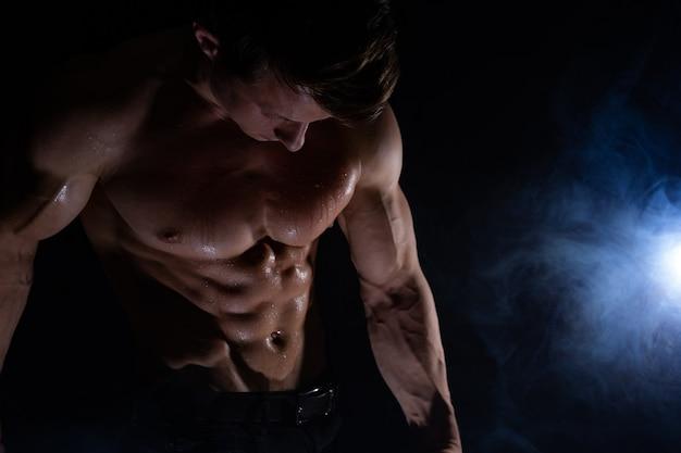 Мускулистый мужчина показывает мышцы, изолированные на черном фоне здорового образа жизни