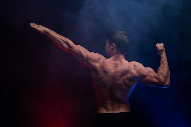 Мускулистый мужчина показывает мышцы, изолированные на черном фоне с цветным дымом. концепция здорового образа жизни.