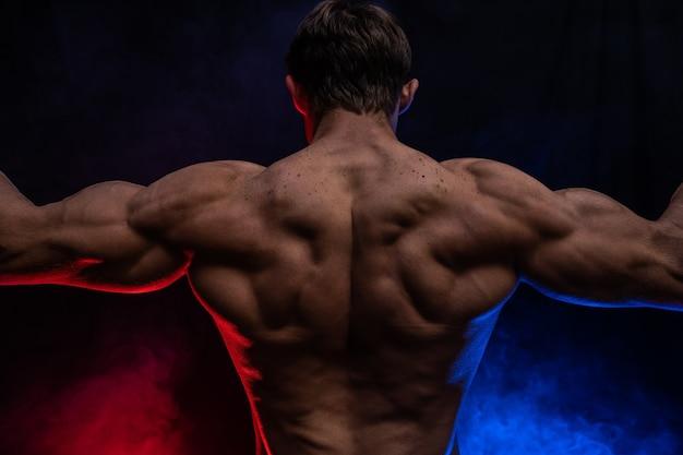 Мускулистый мужчина показывает мышцы, изолированные на черном фоне с цветным дымом
