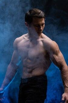 色の煙で黒い背景に孤立した筋肉を示す筋肉男