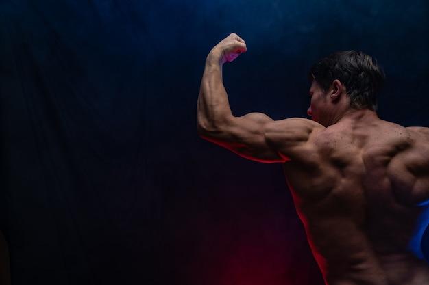 Мускулистый мужчина показывает мышцы, изолированные на черном фоне