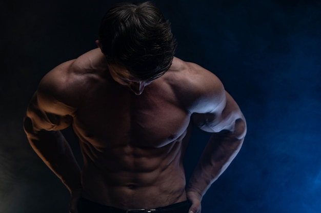 Мускулистый мужчина показывает мышцы, изолированные на черном фоне, здоровый образ жизни
