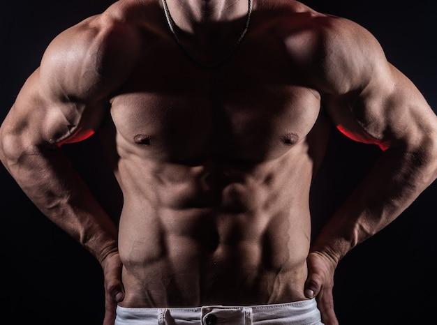 Мускулистый мужчина показывает мышцы, изолированные на черном