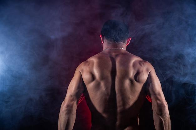 Мускулистый мужчина показывает мышцы на черном фоне концепции здорового образа жизни