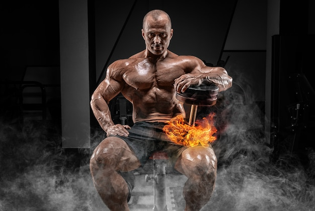Muscular man sits on a bench with dumbbells burning. bodybuilding and powerlifting concept.