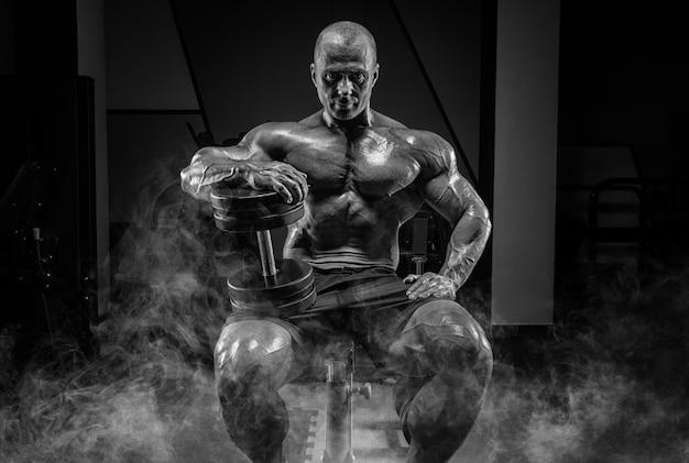 근육 질의 남자는 아령과 연기에 벤치에 앉아 있다. 보디 빌딩 및 파워 리프팅 개념입니다. 혼합 매체