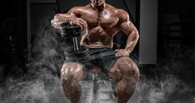 筋肉質の男はダンベルと煙の中でベンチに座っています。ボディービルとパワーリフティングのコンセプト。ミクストメディア