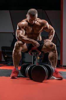 Мускулистый мужчина сидит на скамейке возле огромных гантелей. концепция бодибилдинга и пауэрлифтинга. Premium Фотографии