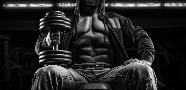 筋肉質の男がジムでダンベルを持ってベンチに座っています。フィットネスとボディービルのコンセプト。