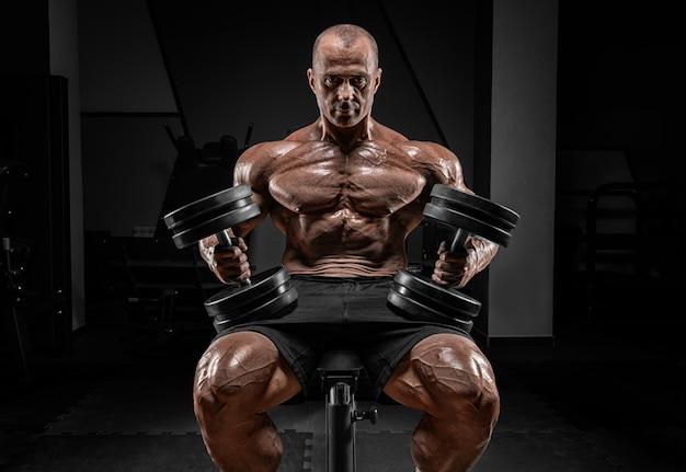 筋肉質の男はダンベルでベンチに座っています。ボディービルとパワーリフティングのコンセプト。
