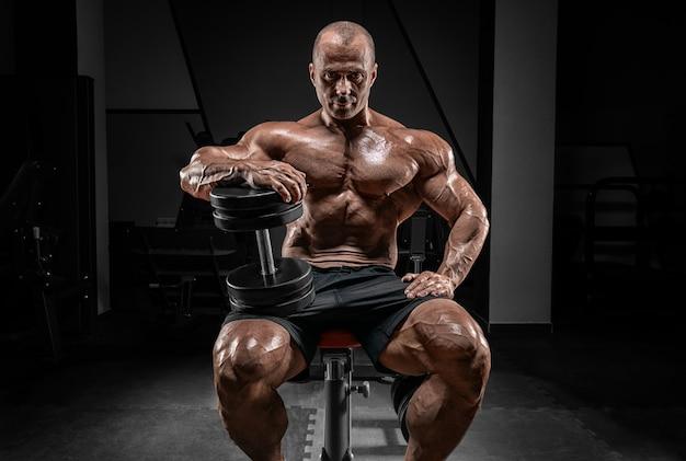 Мускулистый мужчина сидит на скамейке с гантелями. концепция бодибилдинга и пауэрлифтинга. Premium Фотографии