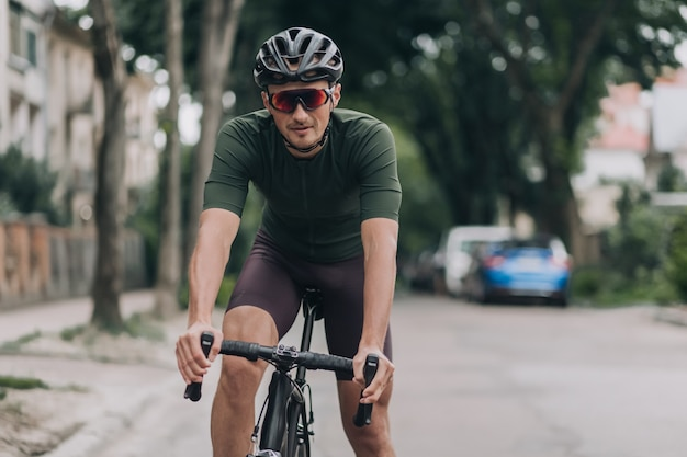 Muscular man in sport clothes riding bike on street