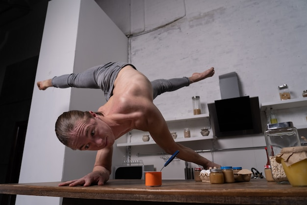 Muscular man stand on the hands in the kitchen and eating yogurt. concept of healthy lifestyle and organic food.