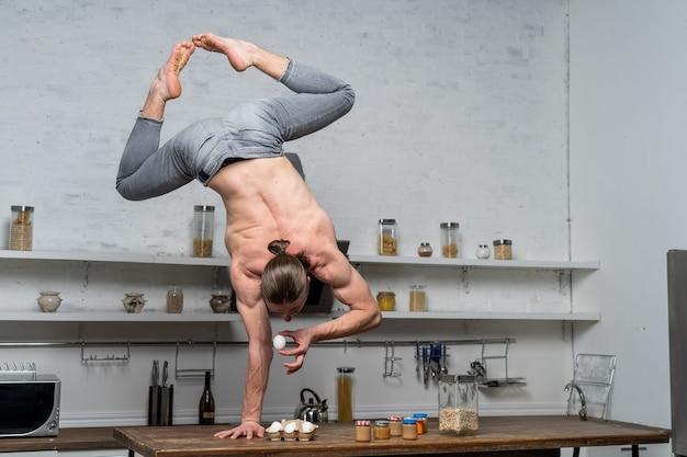 Мускулистый мужчина стоит на одной руке на кухне и держит яйцо