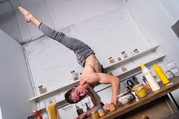 Мускулистый мужчина стоит на одной руке на кухне и держит нож. концепция здорового образа жизни и натуральных продуктов.