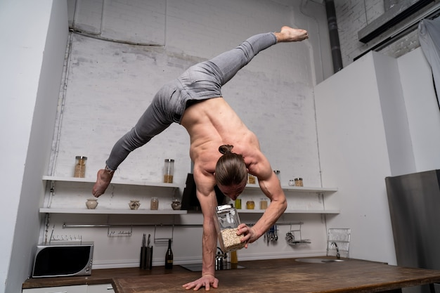 Muscular man stand on one the hand in the kitchen and cooking oatmeal. concept of healthy lifestyle and organic food.
