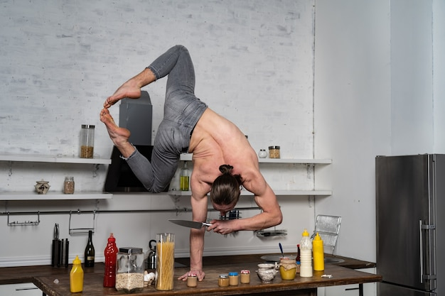 Muscular man stand on one the hand in the kitchen and holding knife concept of healthy lifestyle and...
