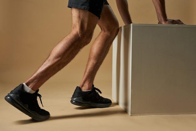 Мускулистый мужчина, стоящий возле батута в комнате в помещении