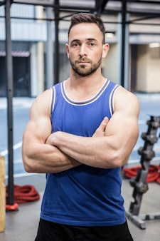 Muscular man standing with arms crossed at the gym