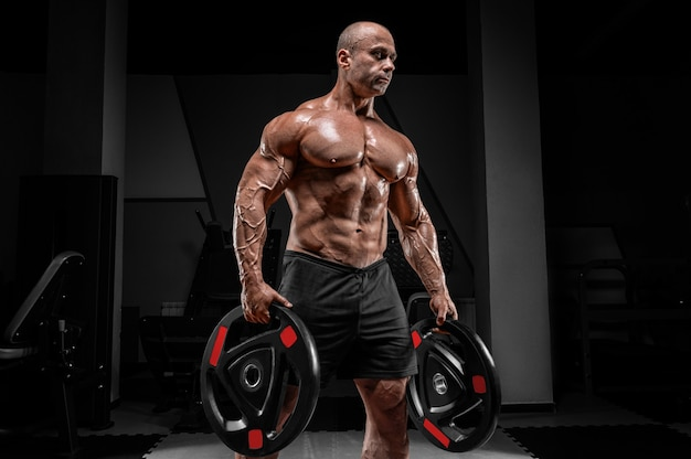Muscular man stands in a gym with barbell discs. bodybuilding and powerlifting concept.