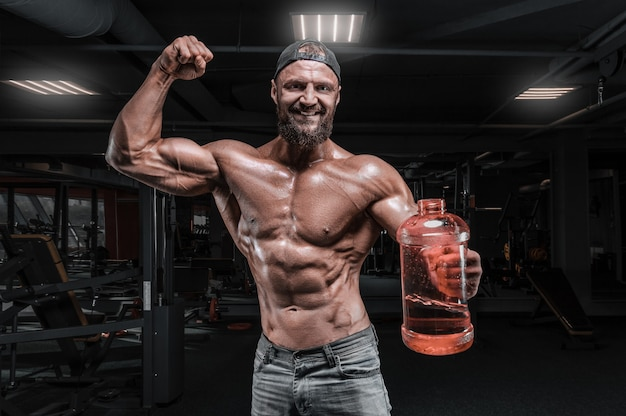 Muscular man stands in the gym with a huge bottle of sports nutrition. fitness and bodybuilding concept. mixed media